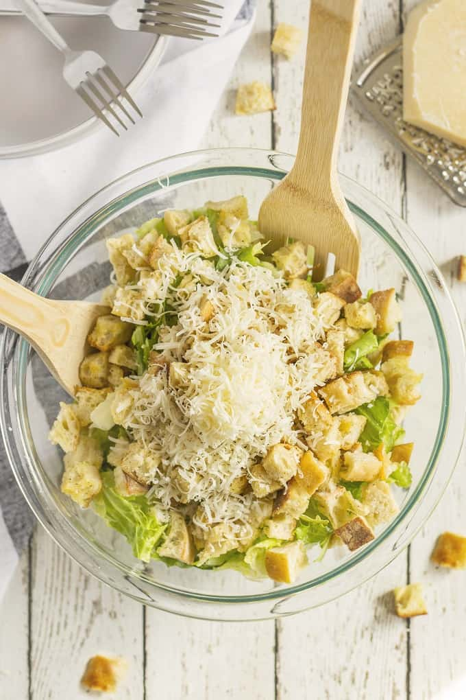 Clear bowl with Caesar salad cruotons and cheese with wooden tossing forks