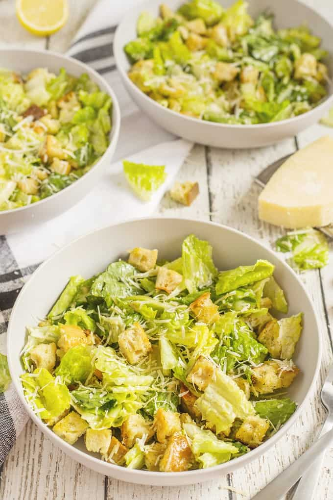 3 serving bowls of Caesar Salad on a wooden board