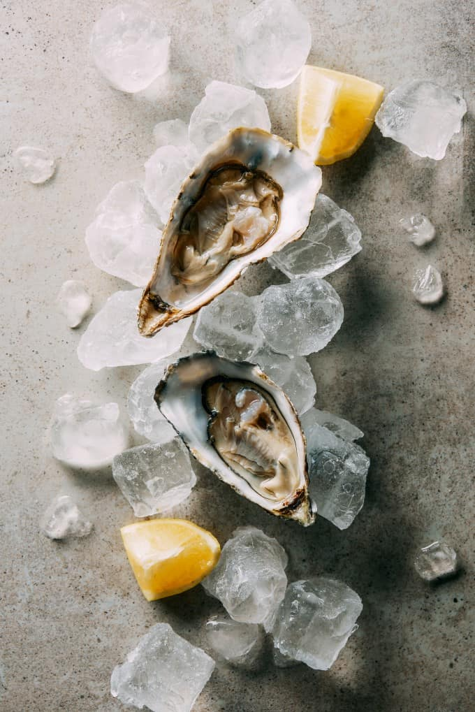 Freshly shucked oysters over ice with lemon wedges