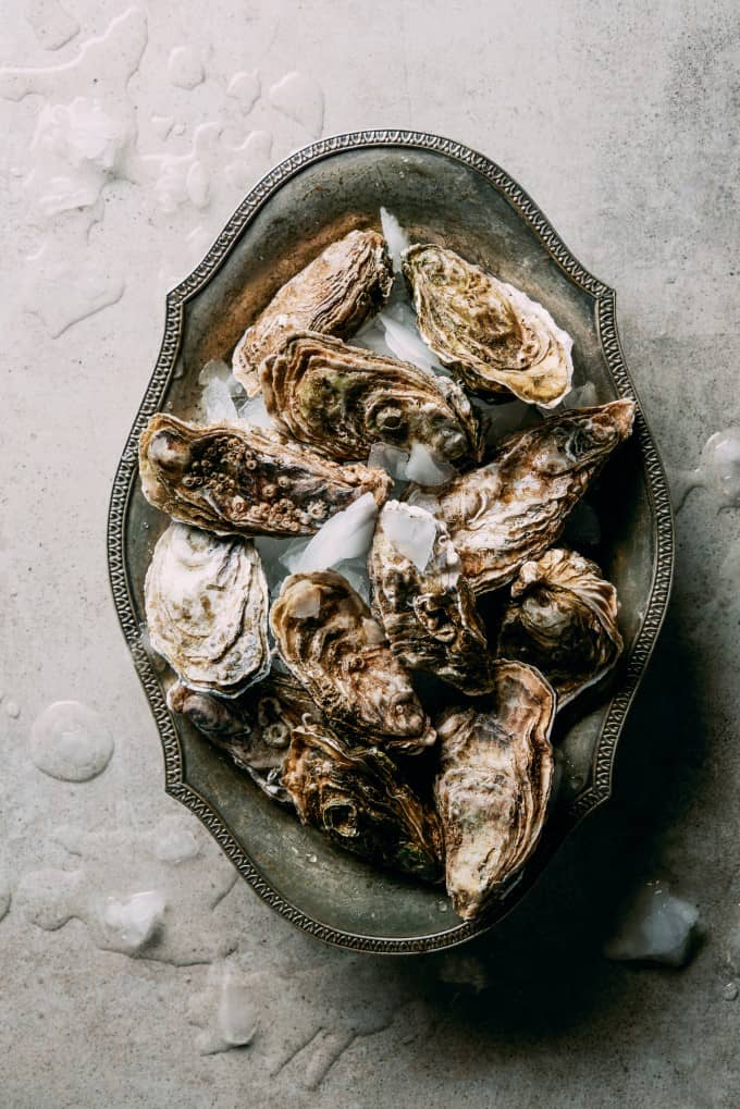 Silver oval bowl filled with whole oysters on ice