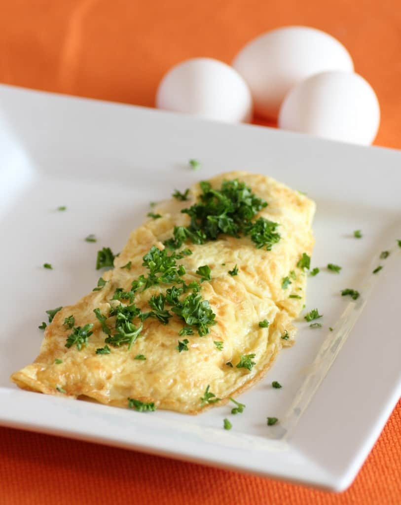 Julia Child's Rolled Omelette on a white plate garnished with parsley and whole eggs in the background