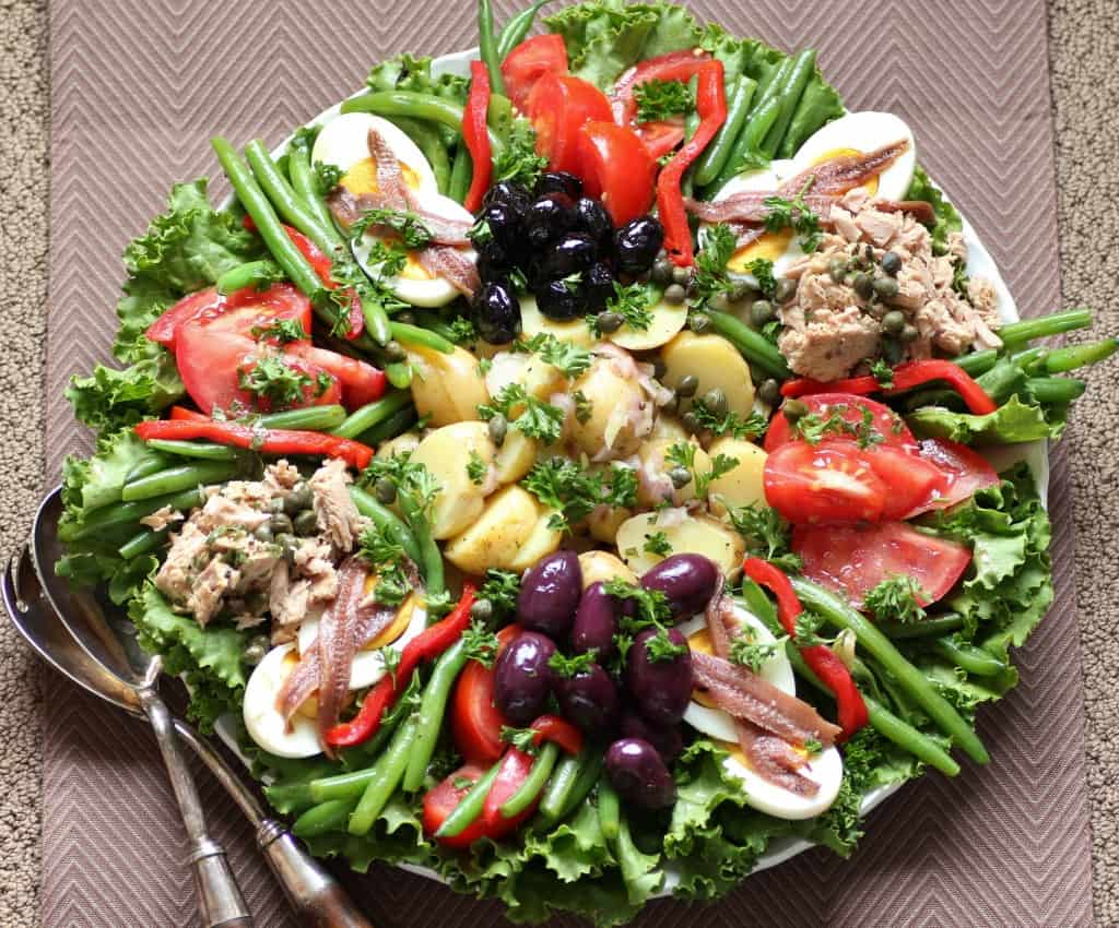 Salade Nicoise on a large round platter with serving spoons on the side.