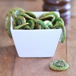 Sauteed Fiddleheads in a square white bowl on a wooden board