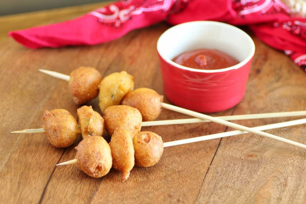 Cowboy Corndogs with a Twist on wooden skewers with a bowl of ketchup for dipping
