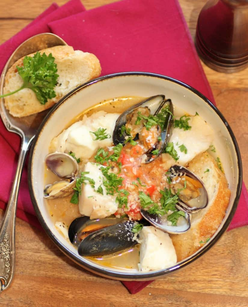 Julia Child's Bouillabaise in a bowl with a spoon and slice of French bread