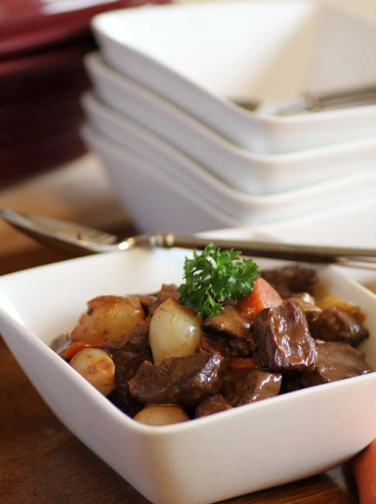 Boeuf Bourguignon in a white bowl with a spoon and other white bowls in the background