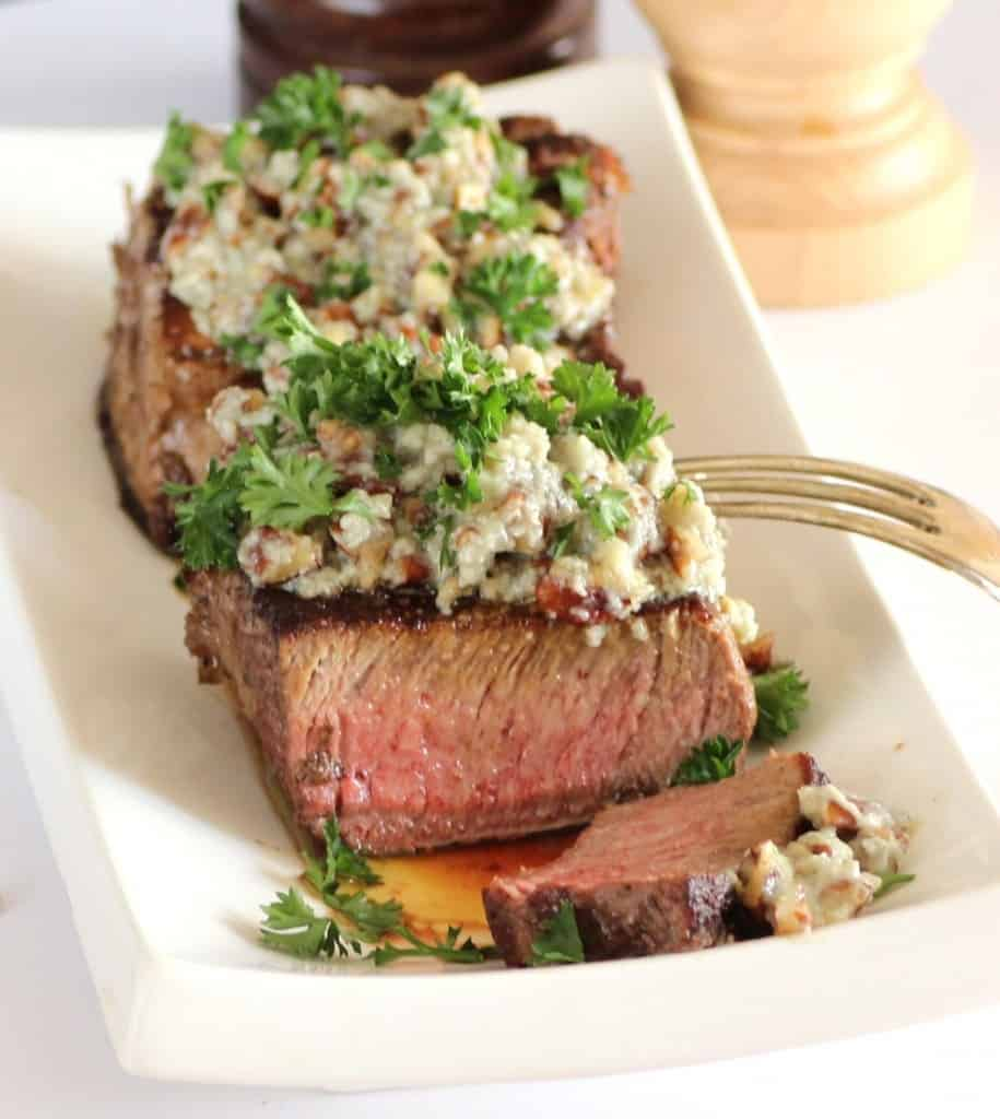 Beef Tenderloin with Stilton Pecan Butter sliced on a white platter with a fork