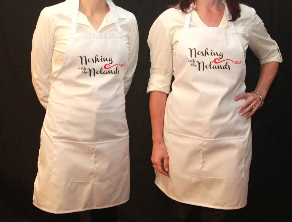 2 models wearing Noshing With the Nolands aprons