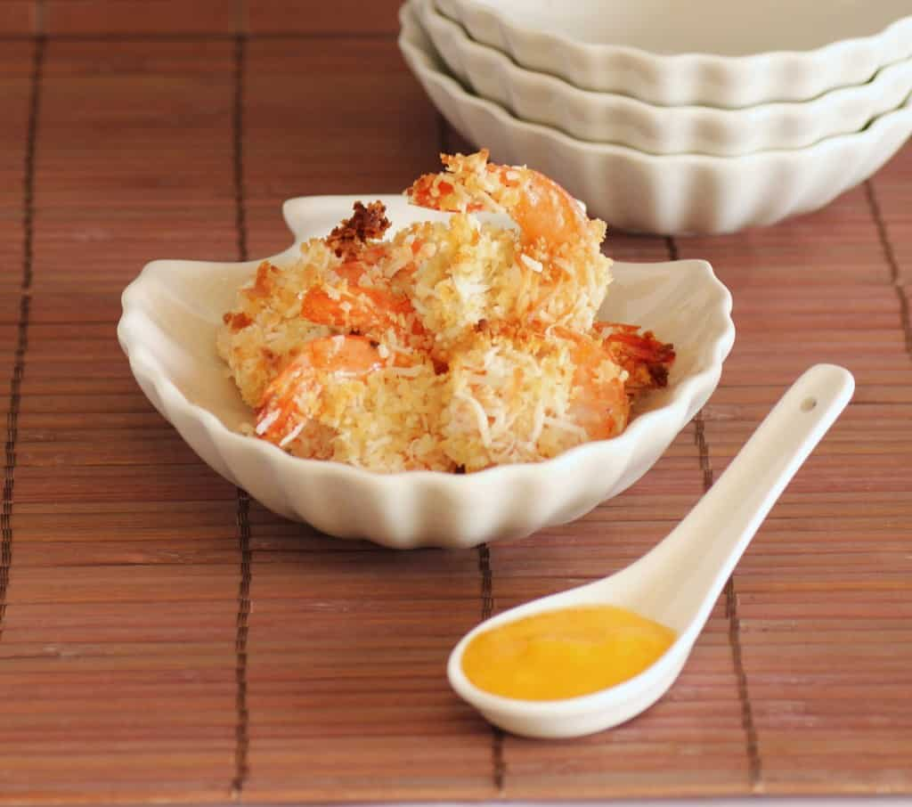 Baked Coconut Shrimp in a clam shell white bowl with a spoonful of mango dipping sauce
