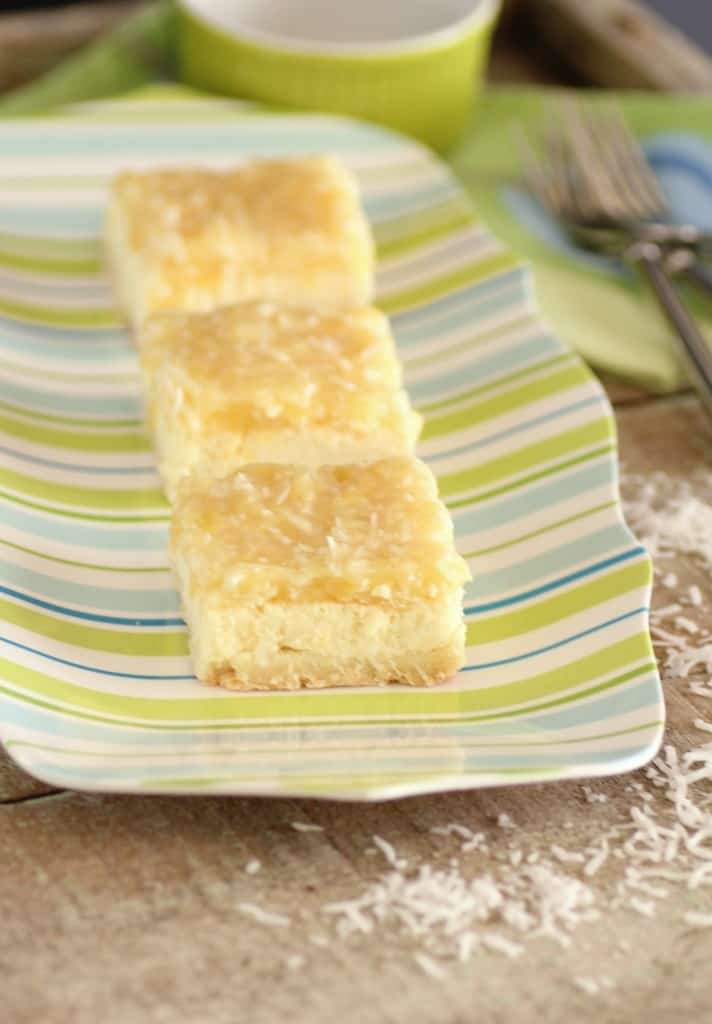 3 Pina Colada Cheesecake Squares on a colourful platewith shredded coconut around the plate