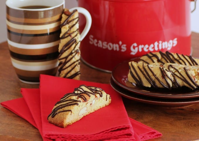 Amaretto Almond Biscotti pieces on a small brown plate and one on a red napkin with a coffee mug