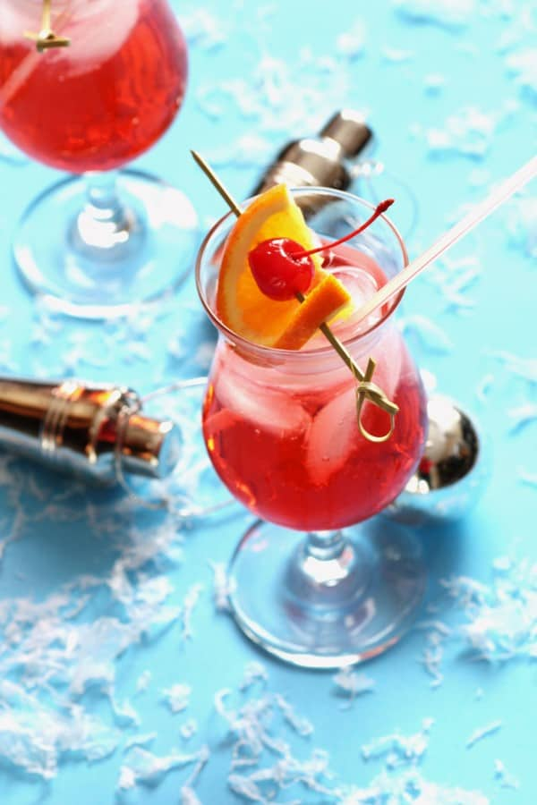 Cherry bomb drink in a glass with a orange slice and a cherry for garnish