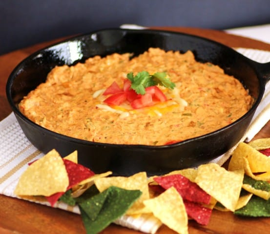 Chorizo Cheese Dip in a cast Iron Skillet with colourful tortilla chips around the pan