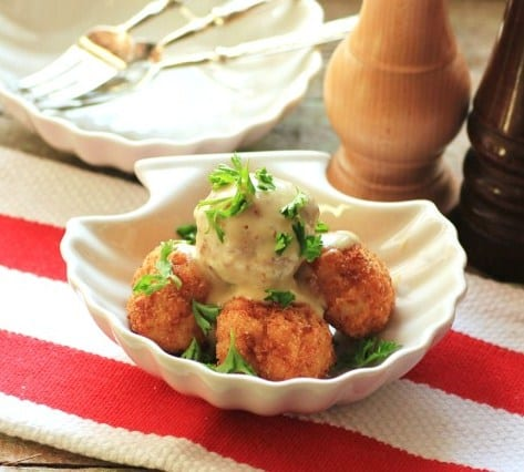 Asiago Stuffed Aranchini with tuffle cream sauce in a white clam shell shaped bowl