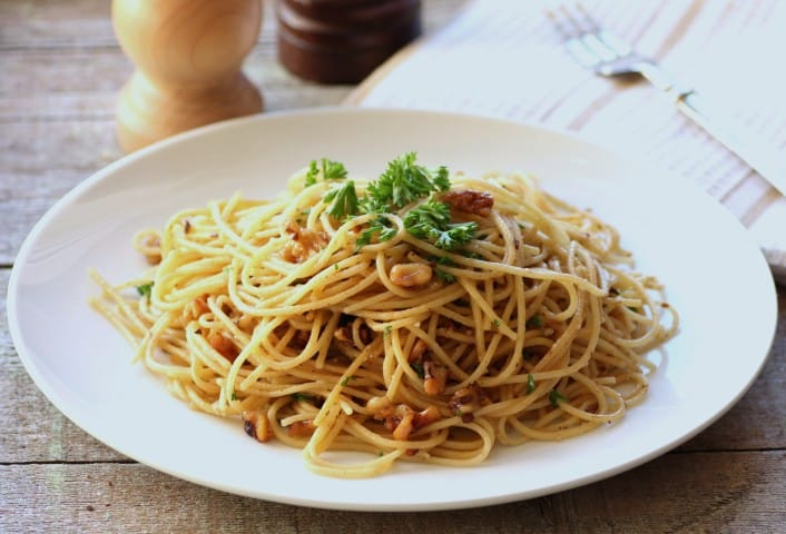 Spaghetti Olio with Walnuts on a white plate sitting on a rough wooden board