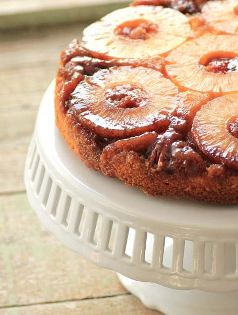 Pineapple Upside Down Cake on a white cake stand.