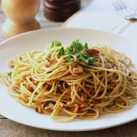 Spaghetti Olie with walnuts on a white plate garnished with fresh parsley