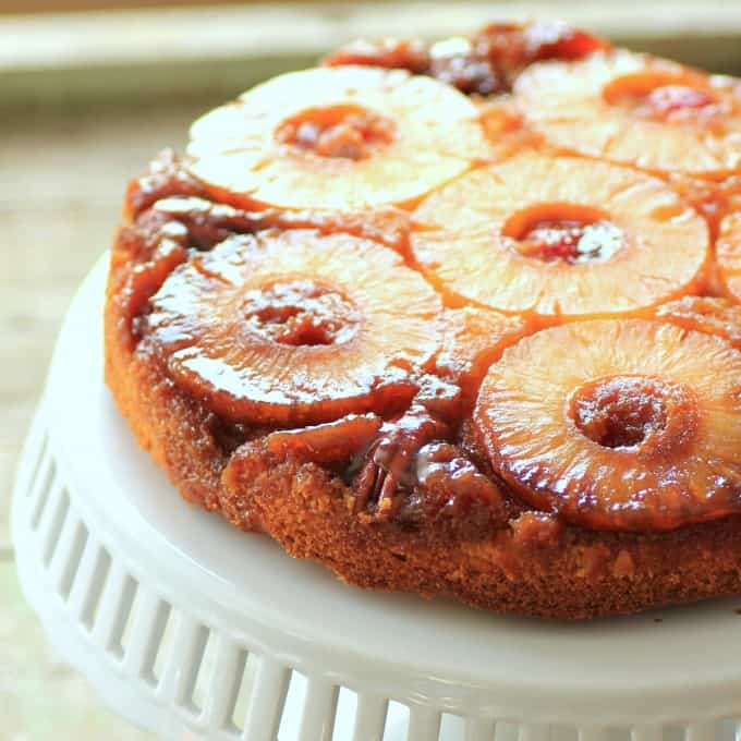 Square photo of Pineapple Upside Down Cake on a white cake stand