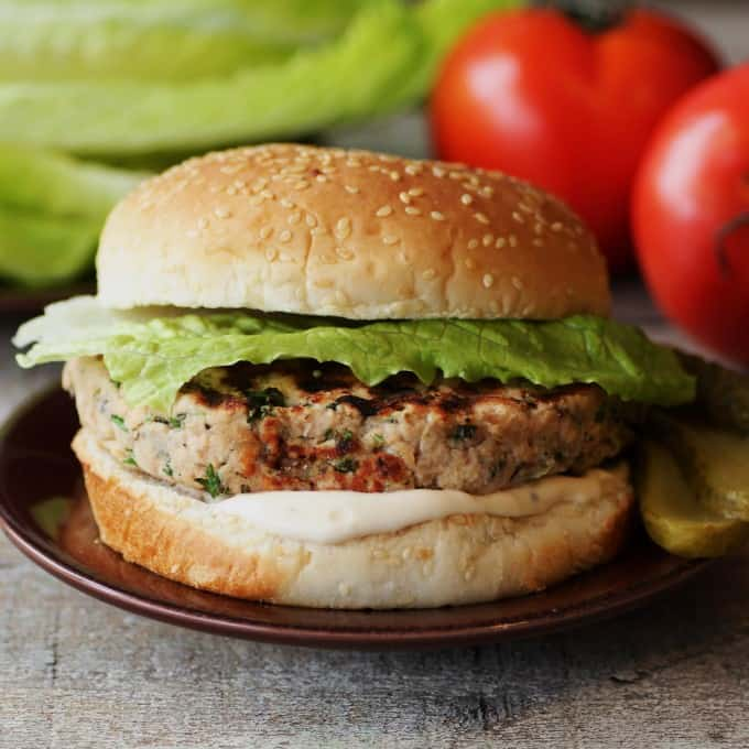 Closeup of a Salmon Burger with tomatoes and lettuce in the background.
