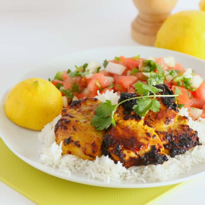 Tandoori Chicken and Tomato Onion Salad on a white plate with lemon