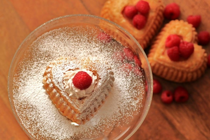 Heart Shaped White Chocolate Cakes with Raspberry Cream on a clear glass plate dusted with powdered sugar