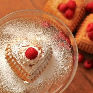 Valentines Day Cakeon a glass plate dusted with icing sugar and a raspberry on top