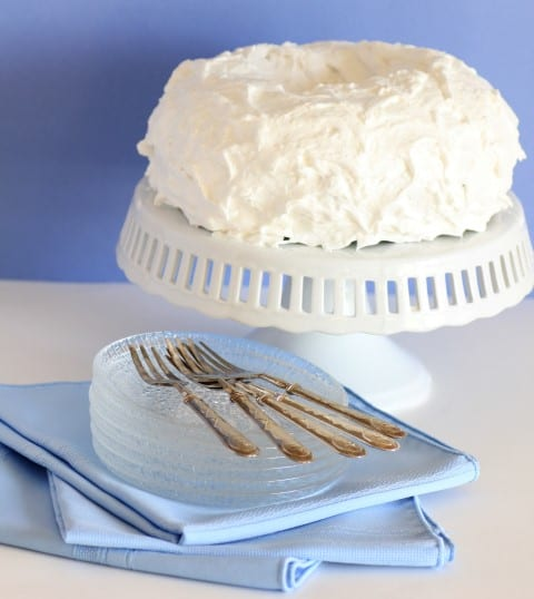 Blue Hawaiian Bundt Cake on a white cake stand with glass serving plates stacked beside it and forks on top of the plates