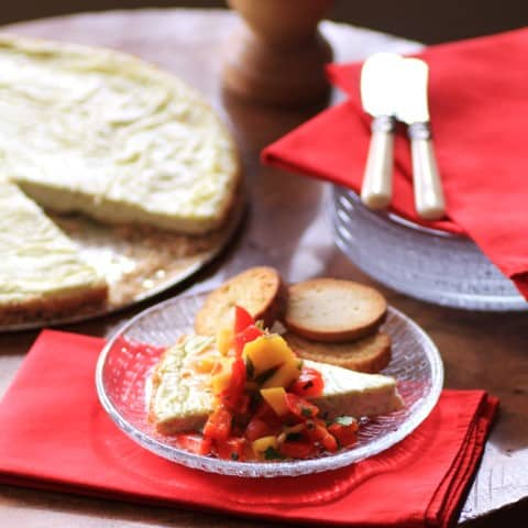 Chevre Torte with Mango and Sweet Pepper Salsa served on a glass plate with some crackers