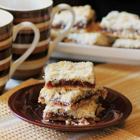 Maple-Date Bars stacked on a small brown plate beside 2 coffee mugs
