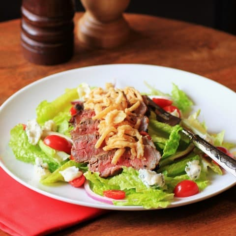 Steak Salad onb a white plate with tomatoes and fried onions as garnish