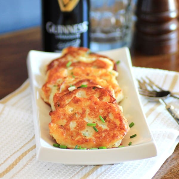 Crispy potato pancakes on a white serving dish with Guinness in the background.
