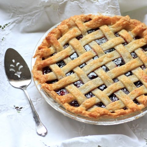 Cherry Blueberry Pie on a white tablecloth with a silver serving spoon