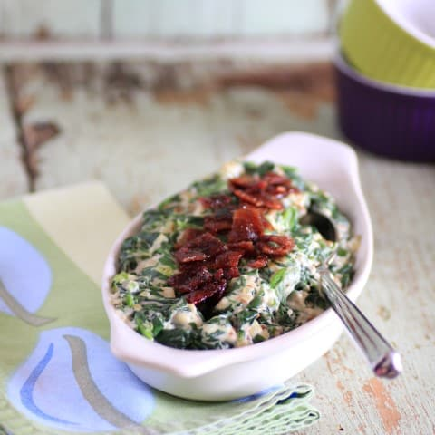 Creamed Spinach in a white bowl with a spoon