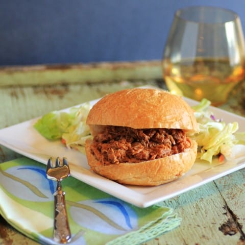 Slow Cooker Pulled Pork Sandwich on a white plate with a glass of white wine