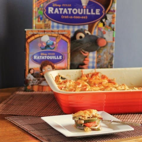 Ratatouille in a red baking dish with a spoon full on a white plate, the DVD Ratatouille in the background