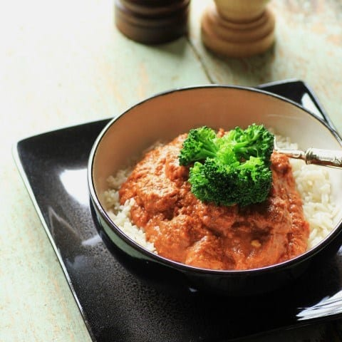 Butter Chicken served over white rice in a black bowl with broccoli on top