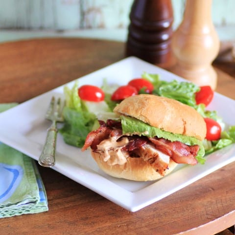 Chipolte Chicken and Bacon Sandwich on a white plate with a green salad sitting on a wooden board