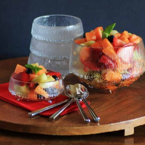 Grand Marnier Fruit Salad in a large bowl also served n a smaller glass bowl on a wooden board