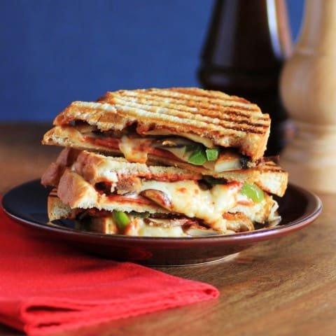 Pizza Panini sandwich cut in half and stack on a small brown plate