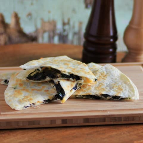 Quesadillas with Mushrooms and Spinach cut in wedges and stacked on a wooden cutting board