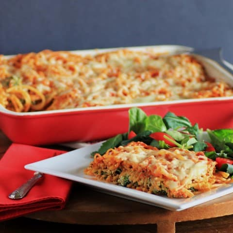 Baked Spaghetti serving on a white plate with the full casserole dish in the background