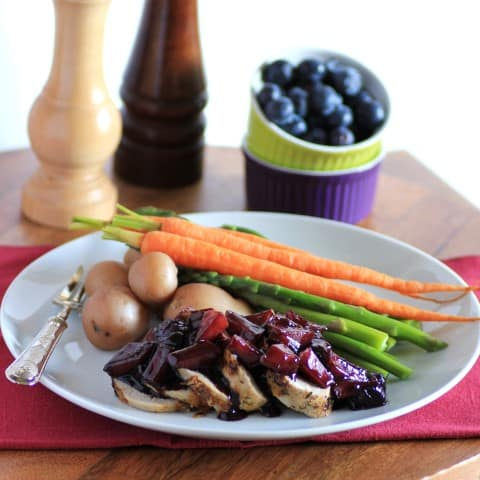 Herbed Pork Tenderloin with Wild Blueberry Sauce sliced on a white plate with carrots, potatoes and asparagus