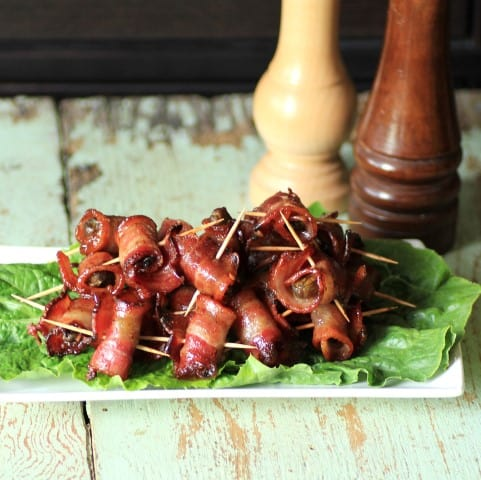 Spicy Caramelized Bacon Wrapped Smoked Oysters on a lettuce leaf on a white serving platter