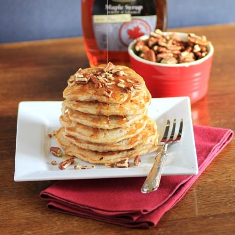 Apple Oatmeal Flapjacks stack high on a white plate with pecans and maple syrup on top