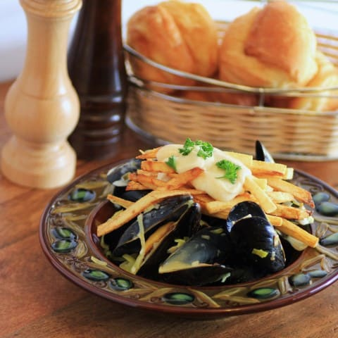 Mussels and Pomme Frites in a brown bowl witha basket of buns in the background