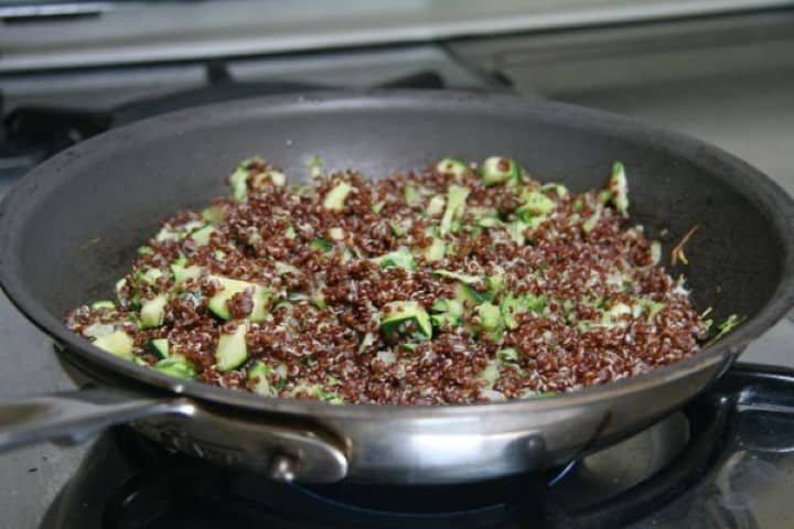 Red Quinoa Zucchini Patti cooking in a fry pan on the stove top