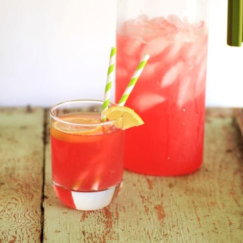 Rhubarb Lemonade in a glass with ice and a straw with a full pitcher behind