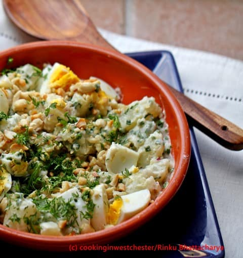 Potato, egg and peanut salad in a red dish with a wooden spoon on the side