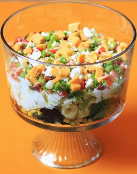 California Layered Salad in a glass trifle dish