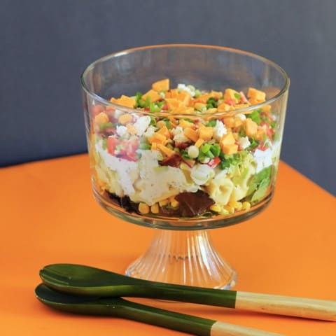California Layered Salad in a triffle dish with salad serving utensils